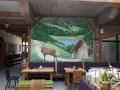 Wandmalerei mit Almhütte und Hirsch in den Bergen