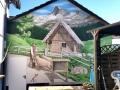 Hauswandbemalung mit Almhütte und Schäfer in den Bergen