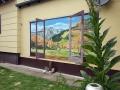 Fassadenmalerei mit Bergpanorama durch ein offenes Fenster