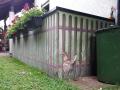 Bemalte Betonwand mit  Wiese und Huhn hinter dem Zaun