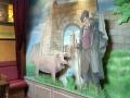 Bemalte Holzkulisse mit Hirt und Schwein vor einer Mauer